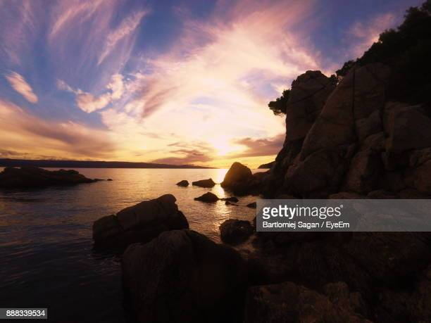 Scenic View Of Sea And Rock Formations At Sunset