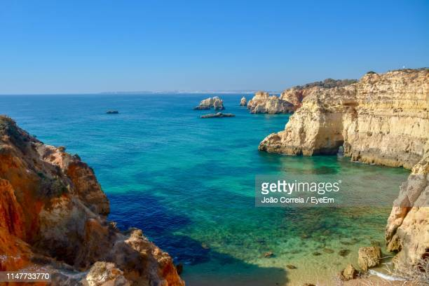scenic view of sea and rocks against clear blue sky - alvor stock pictures, royalty-free photos & images