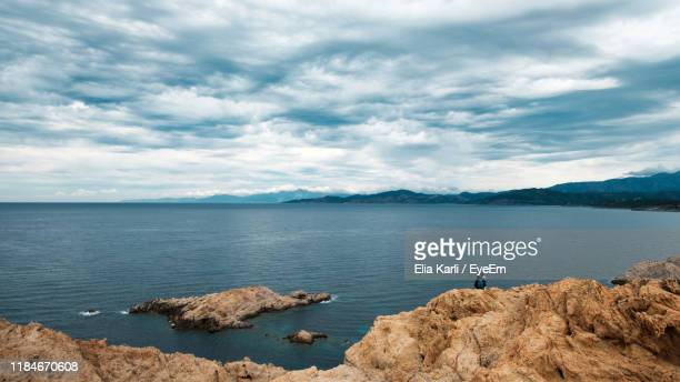 scenic view of sea and rocks against sky - elia karli stock-fotos und bilder