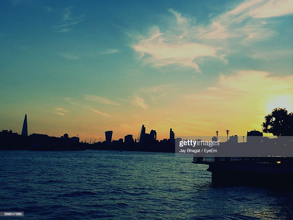 Scenic View Of Sea And Silhouette Buildings Against Sky During Sunset : Stock Photo