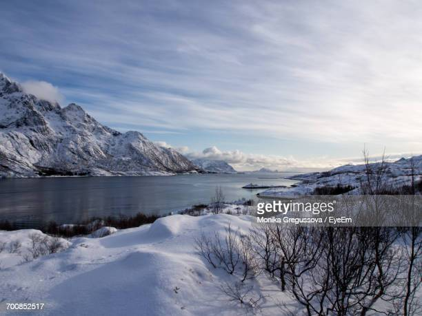 scenic view of sea and snow covered mountains against sky - monika gregussova stock pictures, royalty-free photos & images