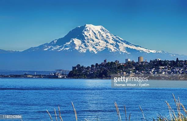 scenic view of sea and snowcapped mountain against blue sky - tacoma stock pictures, royalty-free photos & images