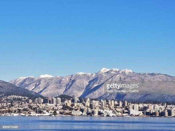 Scenic View Of Sea And Snowcapped Mountains Against Clear Blue Sky