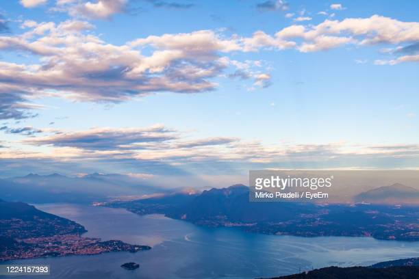 scenic view of sea and snowcapped mountains against sky during sunset - lombardia foto e immagini stock