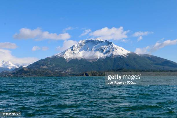 scenic view of sea and snowcapped mountains against sky - joel rogers stock pictures, royalty-free photos & images