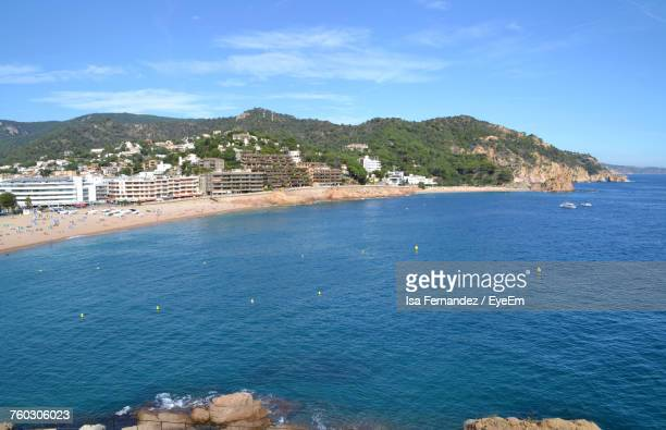 Scenic View Of Sea And Town Against Blue Sky