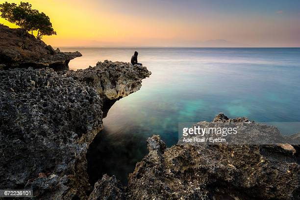scenic view of sea at sunset - ade rizal stock photos and pictures