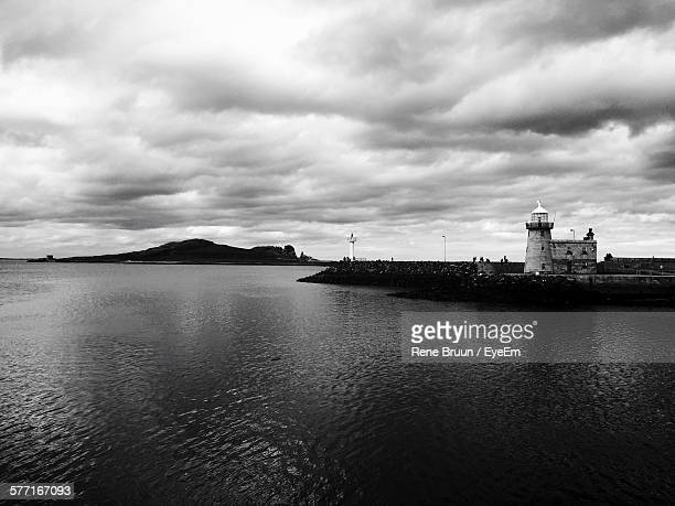Scenic View Of Sea By Baily Lighthouse Against Cloudy Sky At Howth