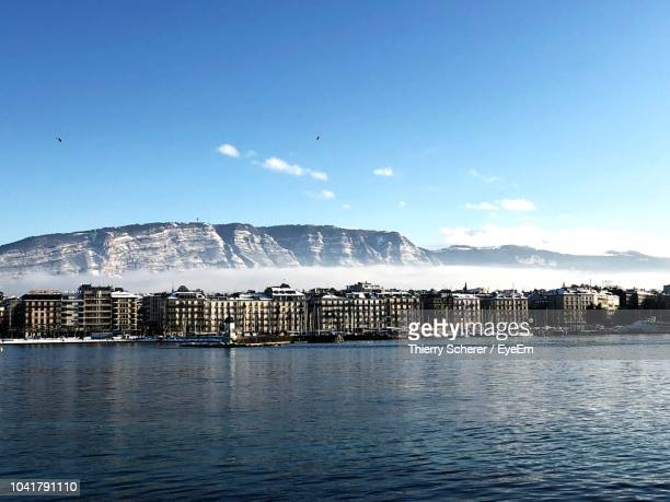 scenic view of sea by buildings against blue sky - geneva switzerland stock pictures, royalty-free photos & images