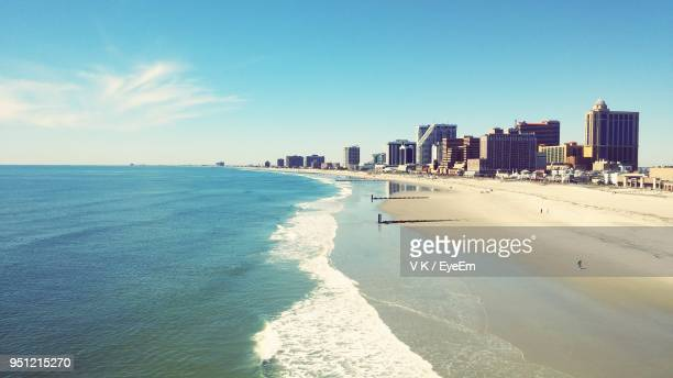 scenic view of sea by buildings against blue sky - atlantic city stock pictures, royalty-free photos & images