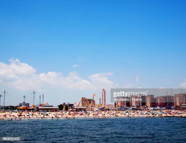 scenic view of sea by buildings against blue sky - coney island stock pictures, royalty-free photos & images