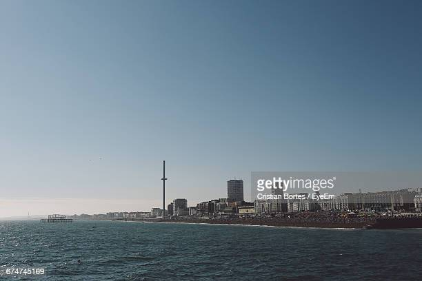 scenic view of sea by buildings against clear sky on sunny day - bortes stock pictures, royalty-free photos & images