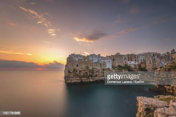 Scenic View Of Sea By Buildings Against Sky During Sunset