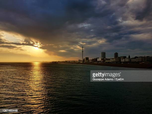 scenic view of sea by buildings against sky during sunset - adamo photos et images de collection