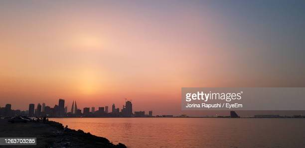 scenic view of sea by buildings against sky during sunset - manama stock pictures, royalty-free photos & images