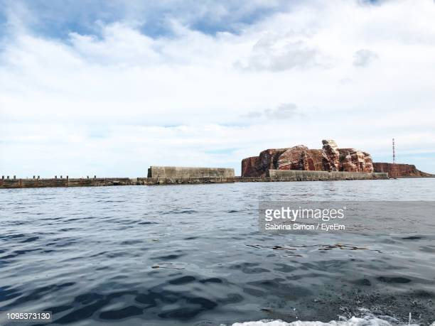 scenic view of sea by buildings against sky - helgoland stock pictures, royalty-free photos & images