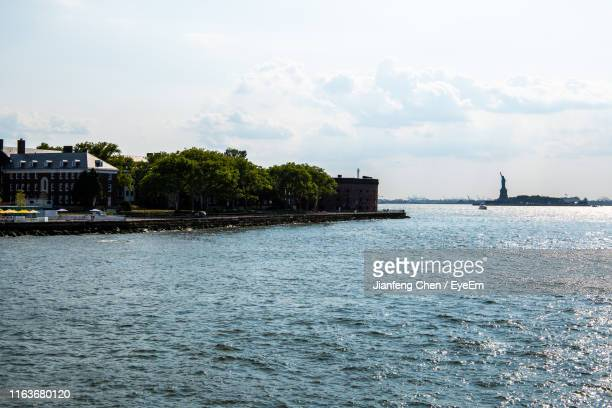 scenic view of sea by buildings against sky - governor stock pictures, royalty-free photos & images