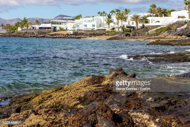 scenic view of sea by buildings against sky - puerto del carmen stock pictures, royalty-free photos & images