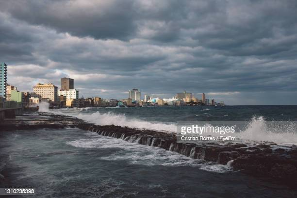 scenic view of sea by buildings against sky - bortes stock pictures, royalty-free photos & images