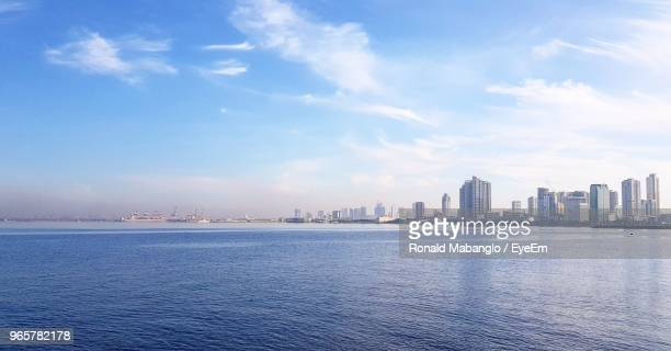 scenic view of sea by buildings against sky - manila bay stock photos and pictures