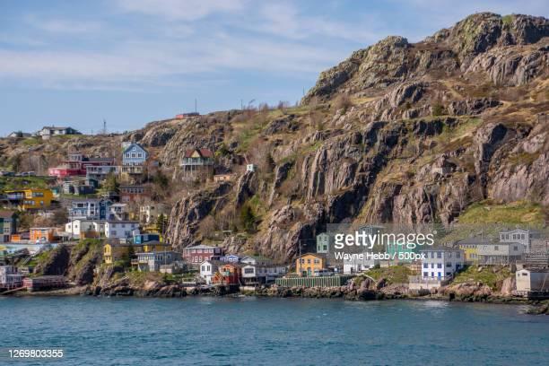 scenic view of sea by buildings against sky, st johns, canada - paisajes de st johns fotografías e imágenes de stock