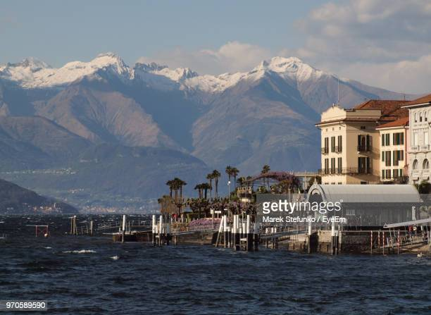 scenic view of sea by buildings and mountains against sky - marek stefunko stock-fotos und bilder