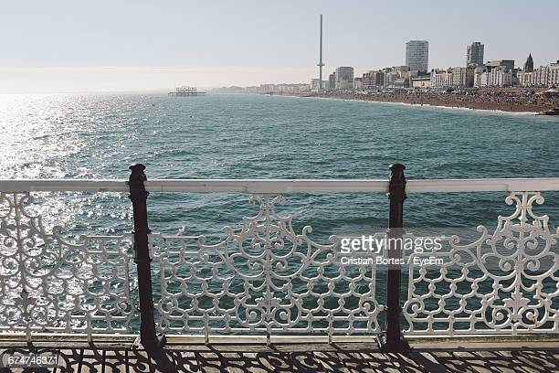 scenic view of sea by buildings in front of fence against sky on sunny day - bortes stock pictures, royalty-free photos & images