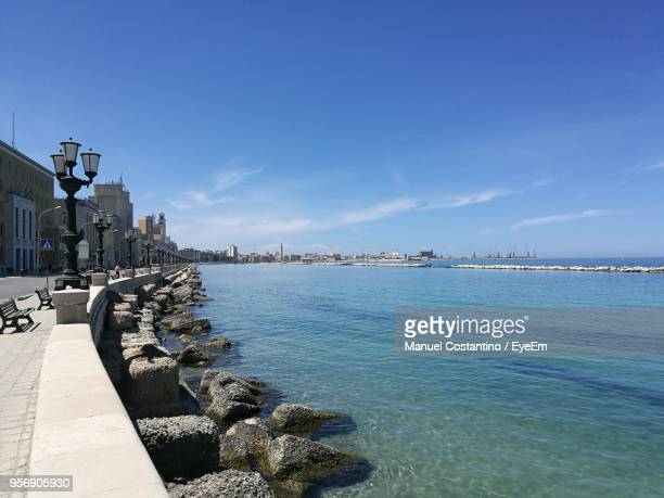 scenic view of sea by city against blue sky - bari stock photos and pictures
