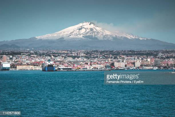 scenic view of sea by city against sky during winter - catania stock photos and pictures