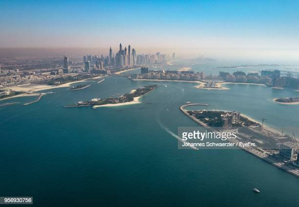 scenic view of sea by city against sky - dubai strand stock-fotos und bilder