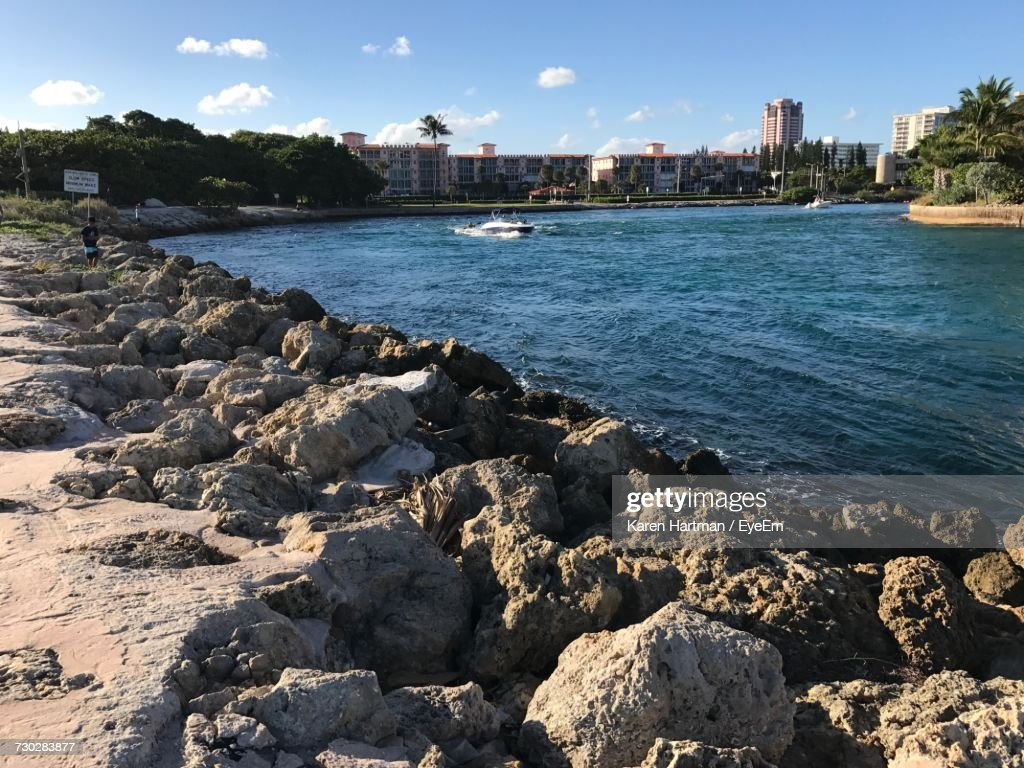 Scenic View Of Sea By Cityscape Against Sky : Stock Photo