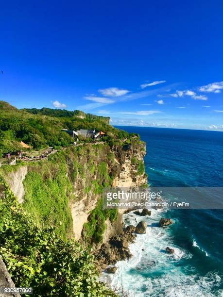 Scenic View Of Sea By Cliff Against Blue Sky