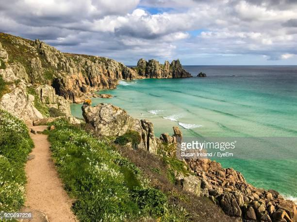 scenic view of sea by cliff against sky - cornwall england stock pictures, royalty-free photos & images