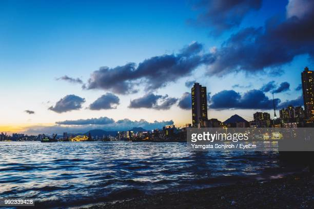 Scenic View Of Sea By Illuminated Buildings Against Sky During Sunset