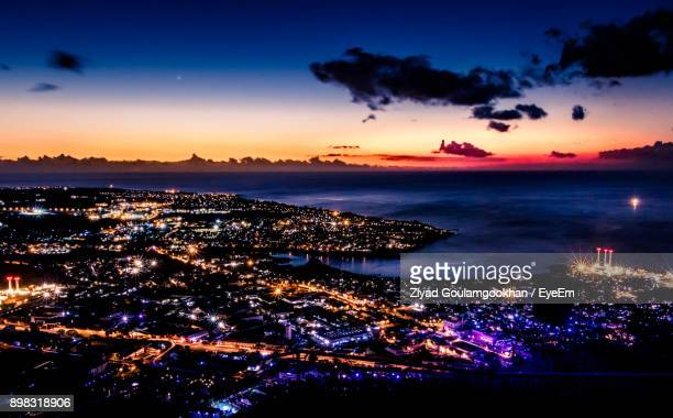 scenic view of sea by illuminated city against sky at sunset - port louis stock photos and pictures
