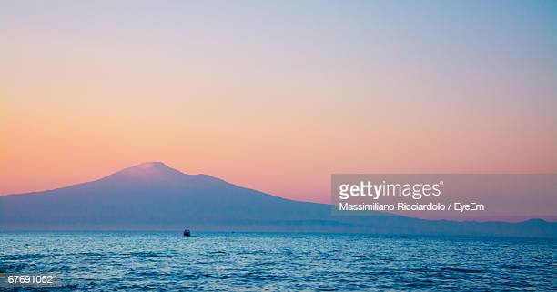 scenic view of sea by mount etna against sky during sunset - mt etna stock pictures, royalty-free photos & images
