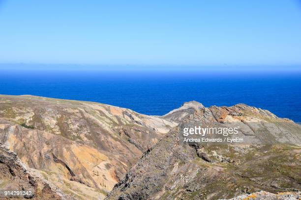 Scenic View Of Sea By Mountain Against Blue Sky