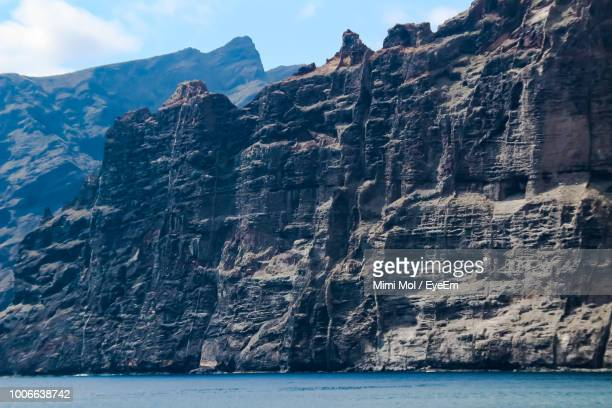 scenic view of sea by mountain against sky - rock wall stock pictures, royalty-free photos & images