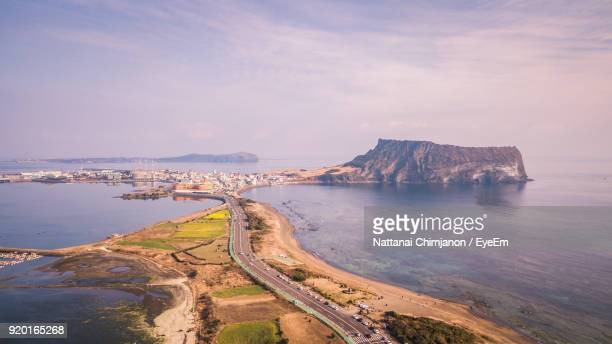 scenic view of sea by mountain against sky - jeju stock-fotos und bilder
