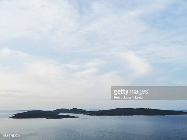 scenic view of sea by mountains against cloudy sky - boban stock pictures, royalty-free photos & images