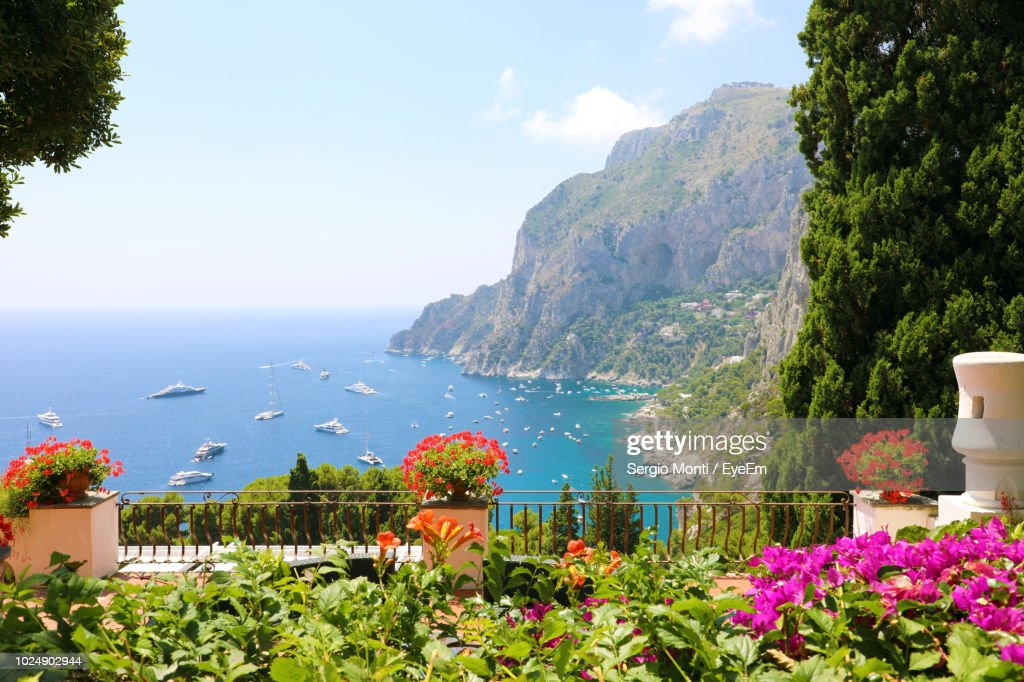 Scenic View Of Sea By Mountains Against Sky : Stock Photo