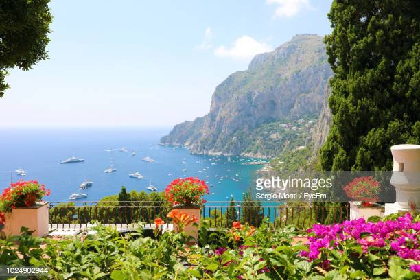 scenic view of sea by mountains against sky - capri stock pictures, royalty-free photos & images