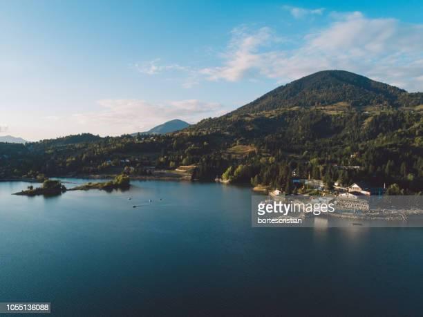 scenic view of sea by mountains against sky - bortes fotografías e imágenes de stock