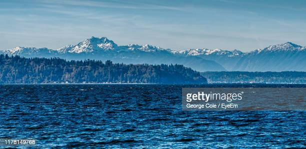 scenic view of sea by mountains against sky - puget sound stock pictures, royalty-free photos & images