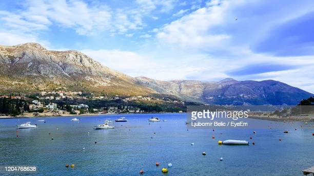 scenic view of sea by mountains against sky - ljubomir belic stock pictures, royalty-free photos & images