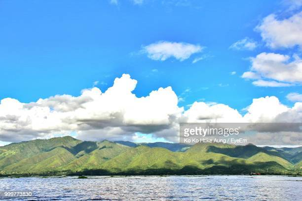 scenic view of sea by mountains against sky - ko ko htike aung stock pictures, royalty-free photos & images