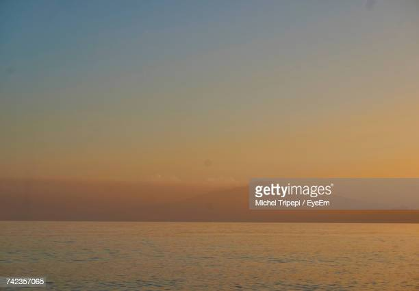 Scenic View Of Sea By Mt Etna Against Sky During Sunset