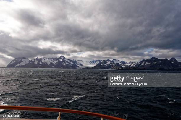 scenic view of sea by snowcapped mountains against sky - gerhard schimpf stock pictures, royalty-free photos & images