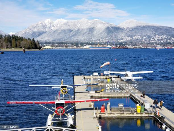 scenic view of sea by snowcapped mountains against sky - grouse mountain stock photos and pictures
