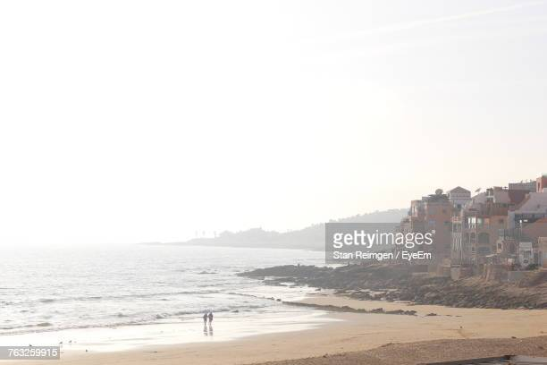Scenic View Of Sea By Town Against Clear Sky